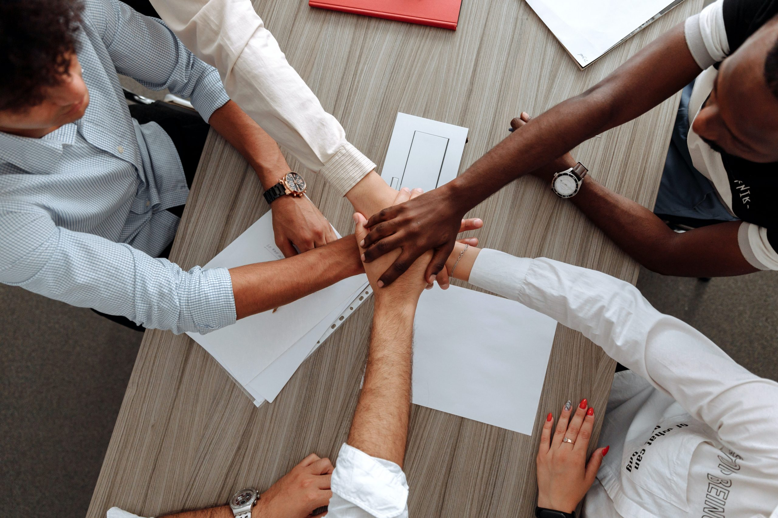 Volunteer hands in a huddle to win